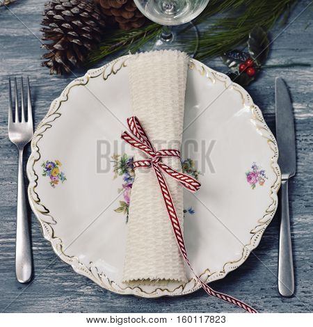 a rustic wooden table set for christmas dinner, with a plate, a knife, a fork, a glass, a napkin tied with a white and red ribbon, and ornamented with some pine cones and some pine tree branches