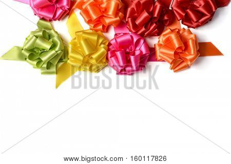 some satin gift ribbon bows of different colors on a white background, with a negative space