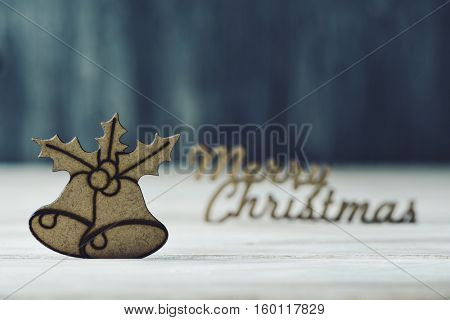 the text merry christmas made in wooden and a wooden ornament in the shape of a pair of bells and a twig of christmas holly, on a rustic wooden surface
