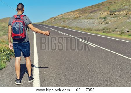 a young caucasian man seen from behind carrying a backpack hitchhiking in a minor road, with his thumb up