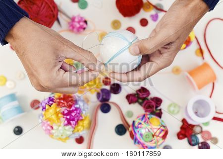 closeup of a young man making a handmade christmas ball rolling blue string around a foam ball and a pile of different haberdashery items on a white table
