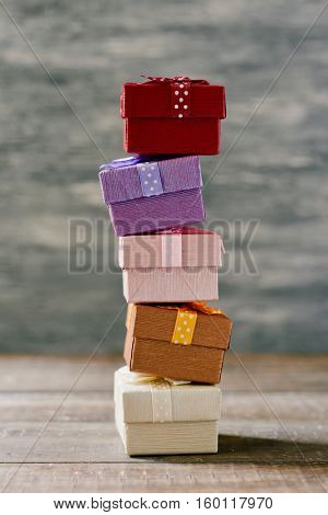 a stack of some cozy gifts wrapped in different papers and tied with ribbons of different colors on a rustic wooden surface
