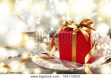 Christmas table setting with festive decor and gift. Sparkling effect