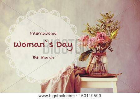 Beautiful flowers in vase on table against color background. Text INTERNATIONAL WOMAN'S DAY, 8TH MARCH