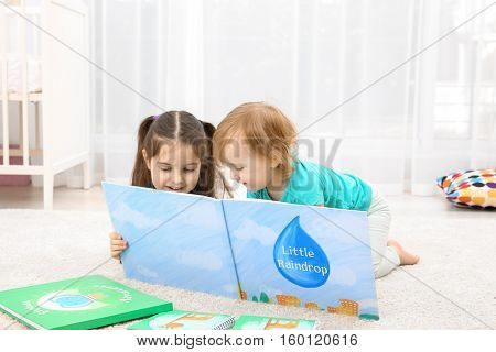 Cute girl reading book with little sister at home
