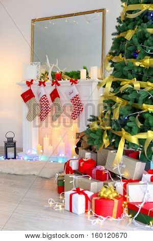 Christmas tree and boxes with presents near fireplace