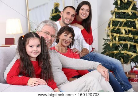 Happy family sitting on sofa in living room decorated for Christmas