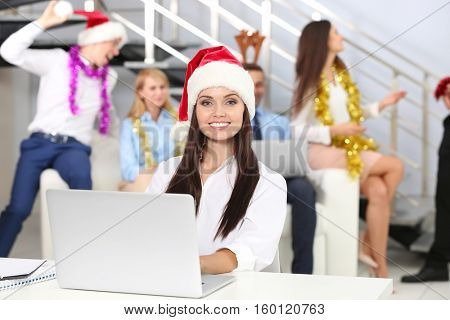 Beautiful young woman wearing Santa Claus hat while working with laptop in office
