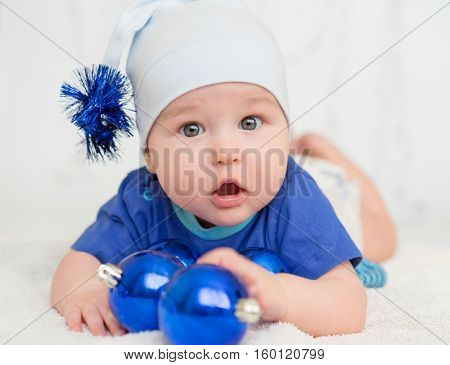baby plays in toys with Christmas decorations on the new year