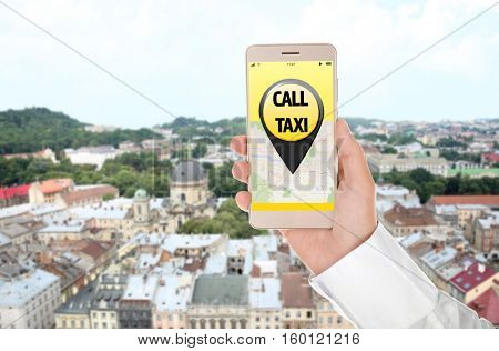 Male hand with smartphone on cityscape background. Taxi service application on screen.