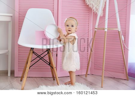Little baby girl on pink wooden screen background