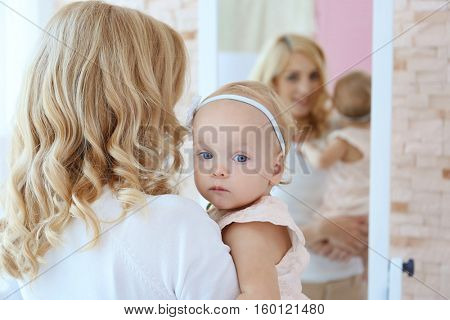 Mother and daughter in room with mirror