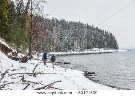 Large Group of people with backpack makes way on a snowy trail at riverside in winter.
