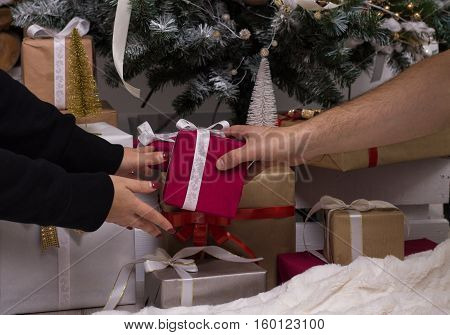 Hands of man giving a Christmas gift to girlfriend. Decorated christmas tree and bunch of gifts on background