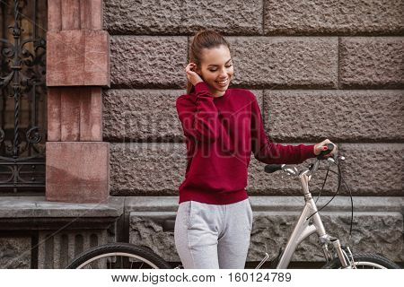 Image of happy woman dressed in sweater walking with her bicycle in the city while standing near wall and smiling. Look aside. Touching hair.