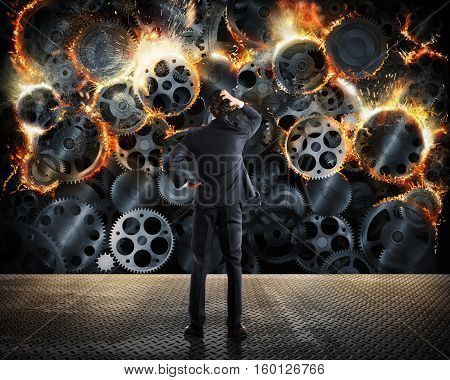Stress concept with overworked businessman desperately looks a gear mechanism burn