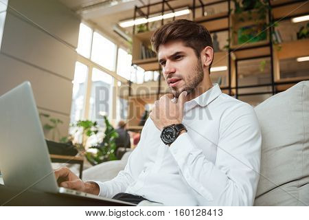 Concentrated businessman dressed in white shirt sitting in cafe and using laptop.