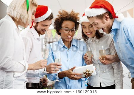 Cheerful colleagues celebrating christmas party in office smiling giving presents.