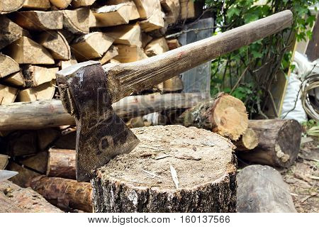ax, hatchet, axe. split a log with an ax. birch  firewood in the background. wood wallpaper