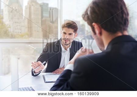 Two businessmen working with laptop in officeTwo concentrated young businessmen working with laptop in office