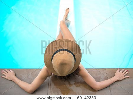 Young woman in big hat relaxing on the swimming pool