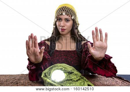 Female psychic or fortune teller with her hands up telling viewer to stop or rejecting. She is isolated on a white background with a crystal ball