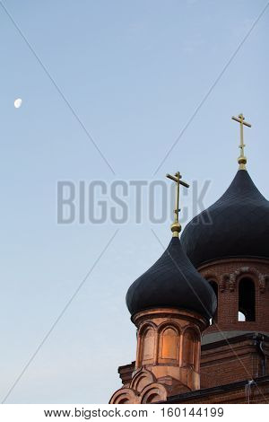 Bell tower of old believer orthodox church at early winter morning, crosses with moon in the sky, vertical