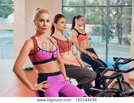 Young women exercising on stationary bicycles in fitness gym. focus on the first girl