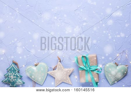Border from christmas toys box with present and fairy lights on blue textured background. Decorative holiday composition. Place for text. Drawn snow.