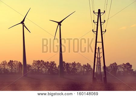 Electricity transmission pylon and wind turbines on field against the sunset