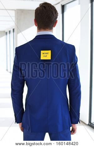 Rear view of young businessman with hire me adhesive note at office