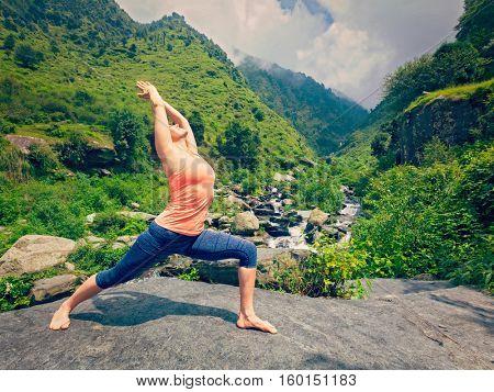 Yoga outdoors - sporty fit woman doing Ashtanga Vinyasa Yoga asana Virabhadrasana 1 Warrior pose posture at waterfall in HImalayas mountains. Vintage retro effect filtered hipster style image.