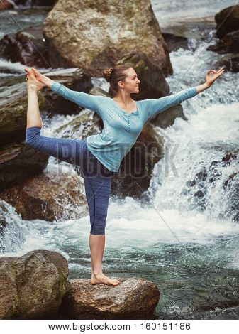 Yoga outdoors - woman doing yoga asana Natarajasana - Lord of the dance balance pose at waterfall in Himalayas. Vintage retro effect filtered hipster style image.