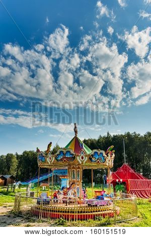 Children's Carousel at an amusement park in the forest and the blue summer sky