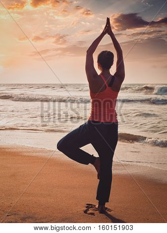 Vintage retro effect filtered hipster style image of Yoga outdoors - sporty fit woman doing Hatha yoga asana Vrikshasana tre pose on tropical beach on sunset
