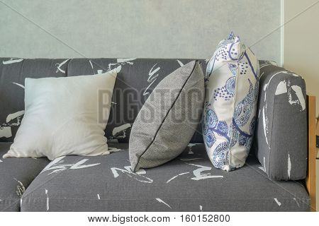 Decorative Pillows Setting On Gray Sofa With Wooden Base In Living Room