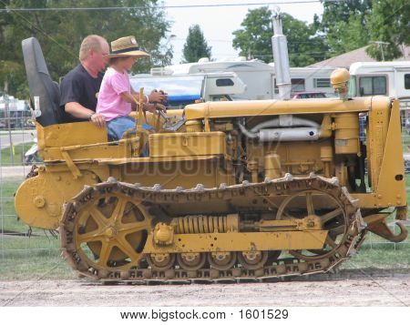 Man Helping Girl Drive Bull Dozer