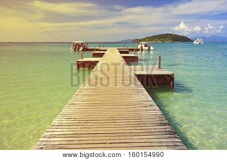 vintage landscape pier quiet in the winter on koh mak beach or mak island harbour and speed boat on the sea with clear sky at Trat Province in Thailand