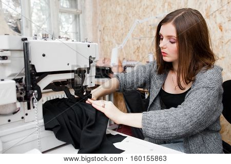 Young beautiful woman sewing at machine. Attractive seamstress working at garment atelier, stitching dark fabric. Designer workshop, clothes making concept