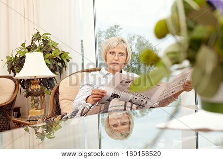 Woman in glasses sitting in comfortable chair and reading fresh news in newspaper