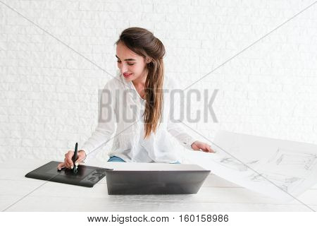 Woman retouching sketch on laptop, free space. Young female designer working with row draft using graphic tablet in workshop, white background. Business, art, creativity concept