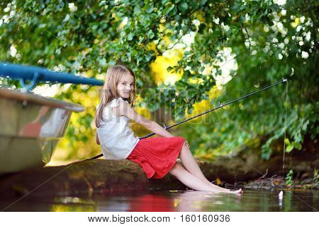 Cute Little Girl Fishing With A Fishing Rod By A River