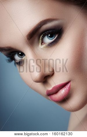The girl's face close up. Beauty stock photos. Perfect skin beautiful professional makeup. gray background