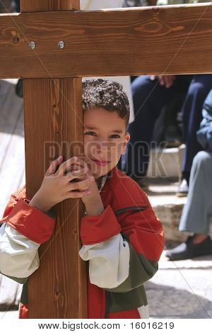 JERUSALEM - APRIL 21: Child with cross, come to Holy Sepulchre for pray, after a Crucession, in front of Temple, on Good Friday April 21, 2006 in Jerusalem, Israel.