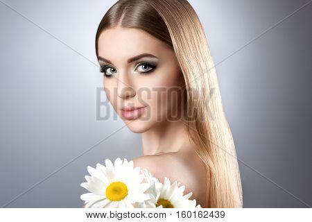 Portrait Of A Young Attractive Girl With A Beautiful Make-up And Daisies.