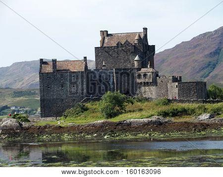 Eilean Donan castle, celtic medieval scottish famous monument at lake (loch Duich) in Highlands in SCOTLAND with cloudy sky in warm summer day, GREAT BRITAIN on AUGUST.