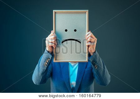 Businesswoman is pessimistic about her future in corporate business holding printed sad smiley emoticon over her face