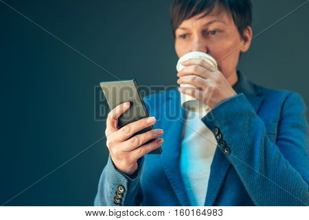Satisfied young adult businesswoman drinking coffee to go and looking at the mobile phone