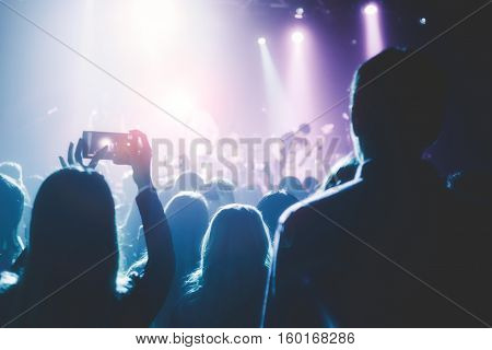 Female hands holding their smartphone and photographing concert. The concert hall is full of people at a rock concert