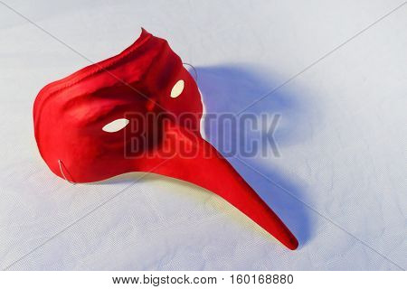 Close up of a red paper carnival mask (homemade product) with blue shadow on white. Fashion background.